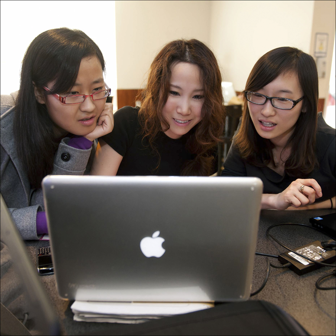 3 Asian women viewing laptop  in academic setting  by Brian Smith