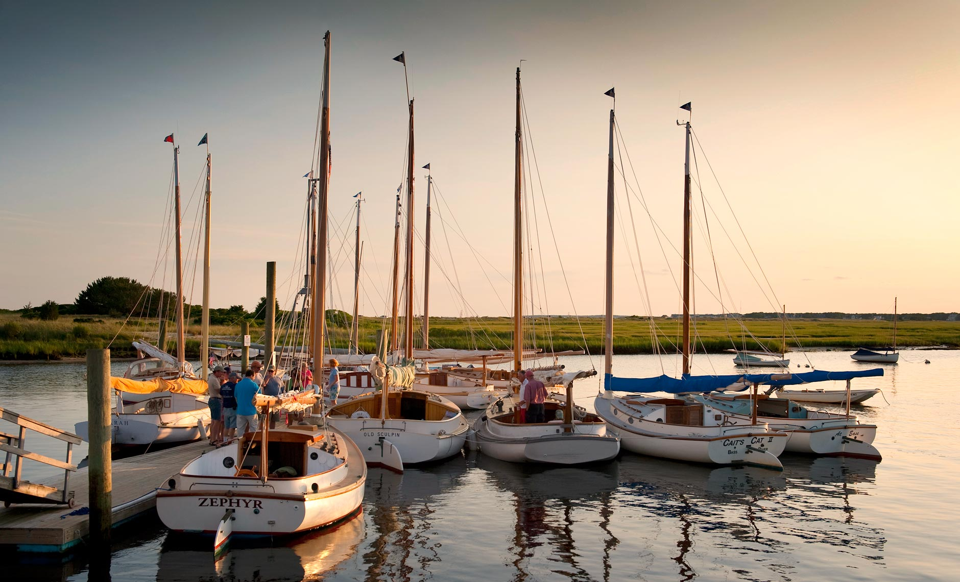 A gathering of catboats at dusk at West Dennis , MA