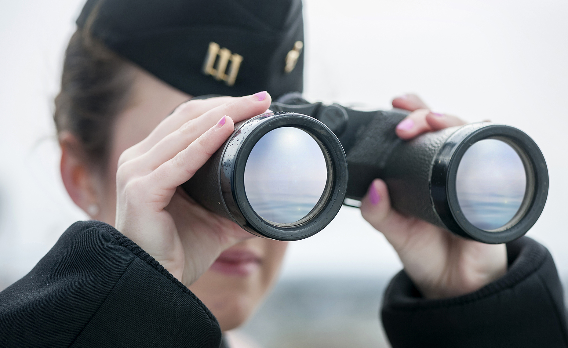 Close up of Binoculars being held by female cadet from Mass Maritime Academy