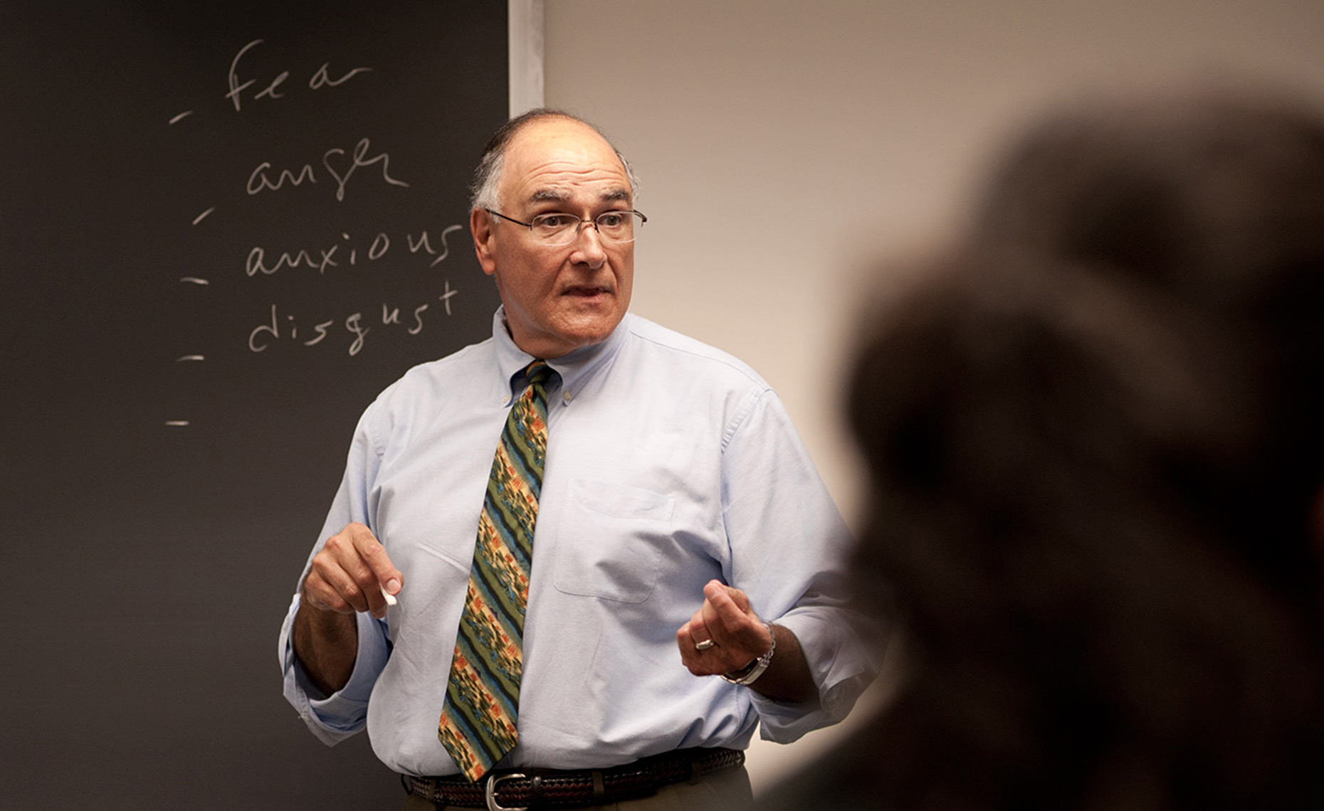male professor lecturing at chalkboard at Bentley University