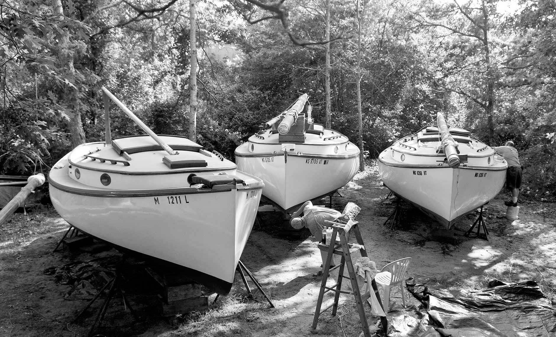 Black and white photograph of 3 catboats in boatyard