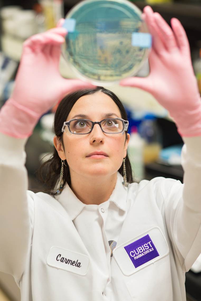 female lab worker holding up petri dish at Cubist