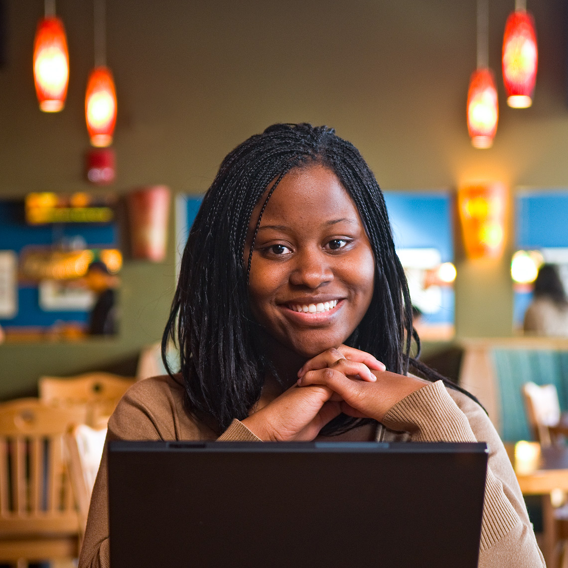 Portrait of black female college student with laptop in the foreground.