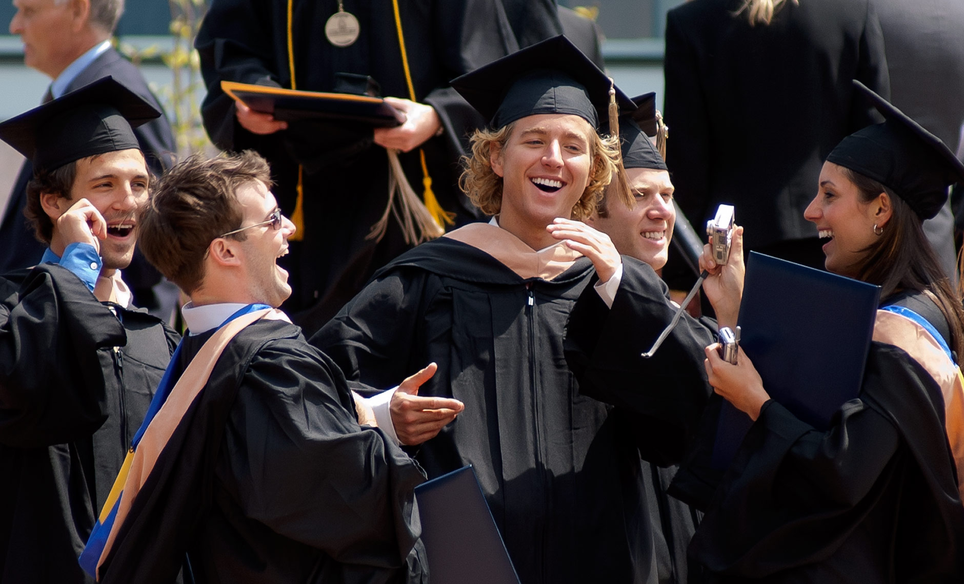 College graduates laughing in caps and gowns