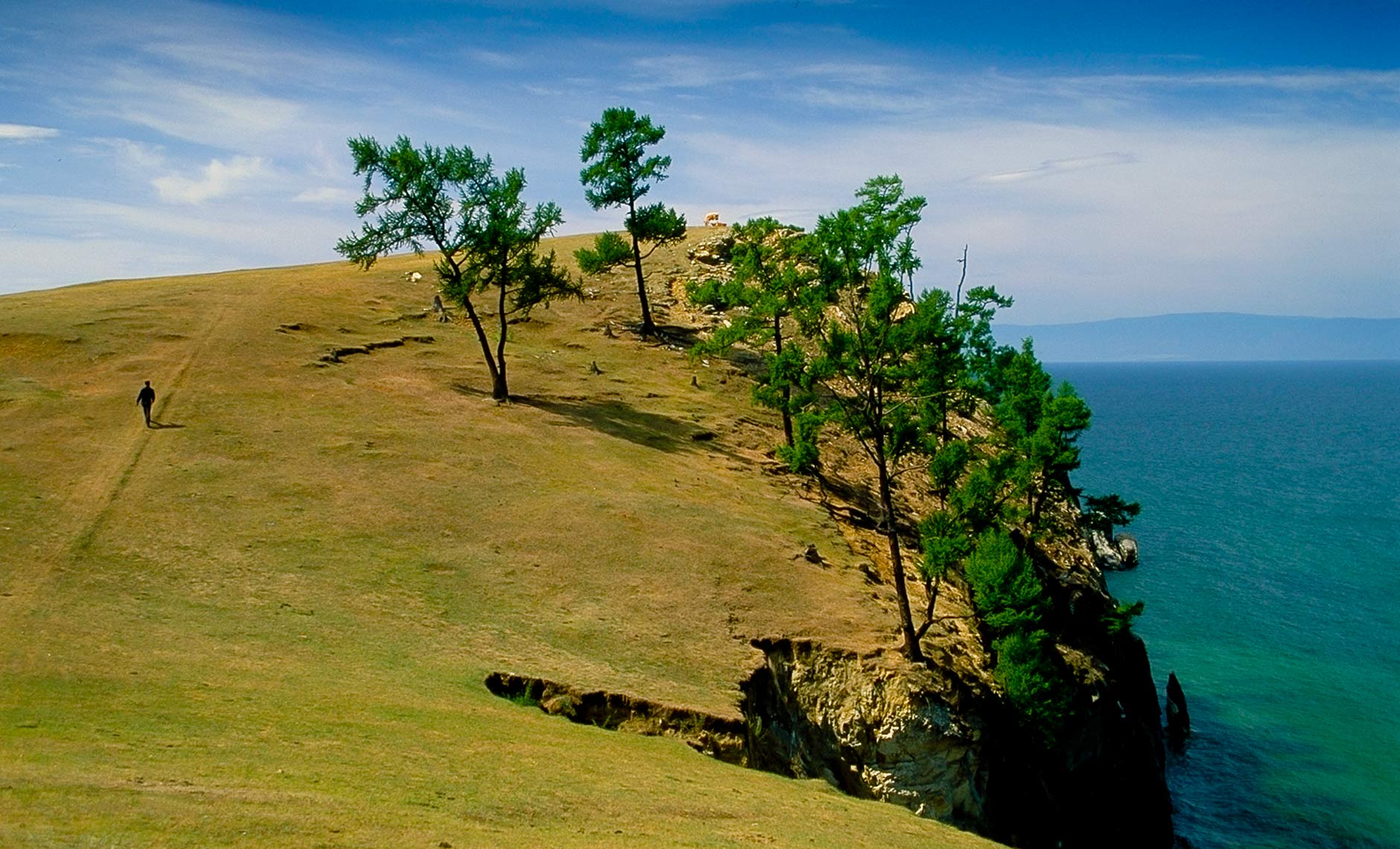 man walking up hillside near Lake Baikal, Russia