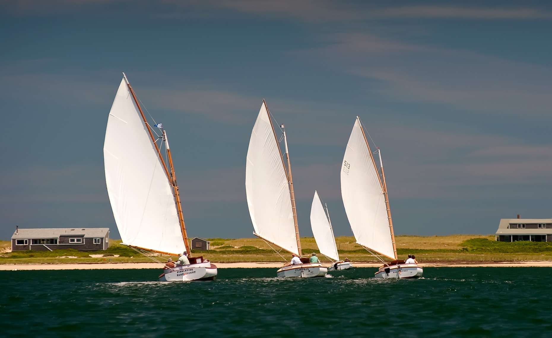 three catboats racing in Nantucket Harbor