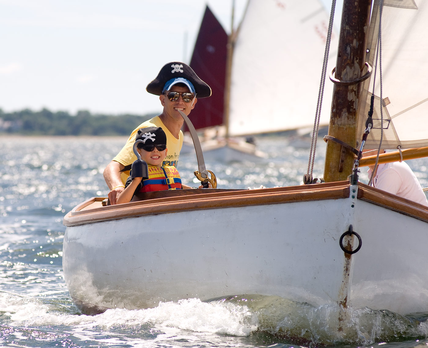 Child and father wearing pirate hats on sailboat